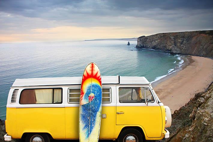ビーチ沿いで黄色いバンとサーフボード